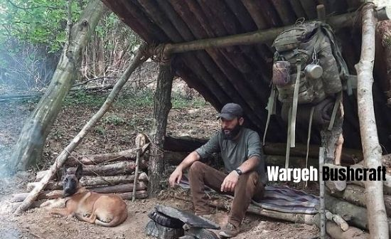 Wargeh Bushcraft with his dog Agir resting inside his wooden log cabin