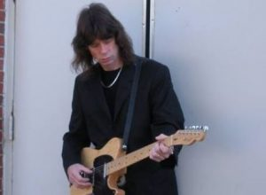 Photo of Scott Wahlberg holding his guitar